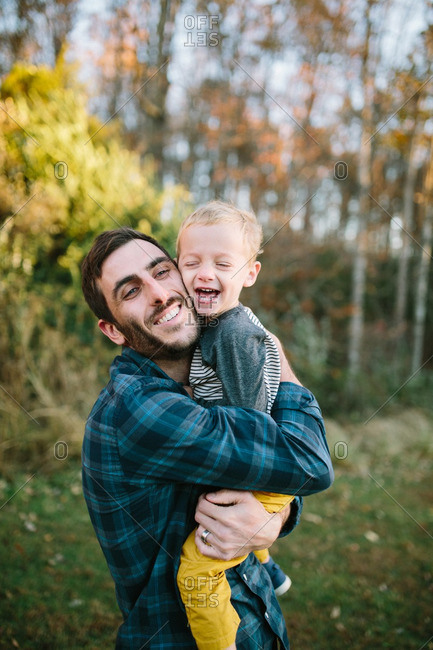 Father hugs his toddler son outdoors in autumn