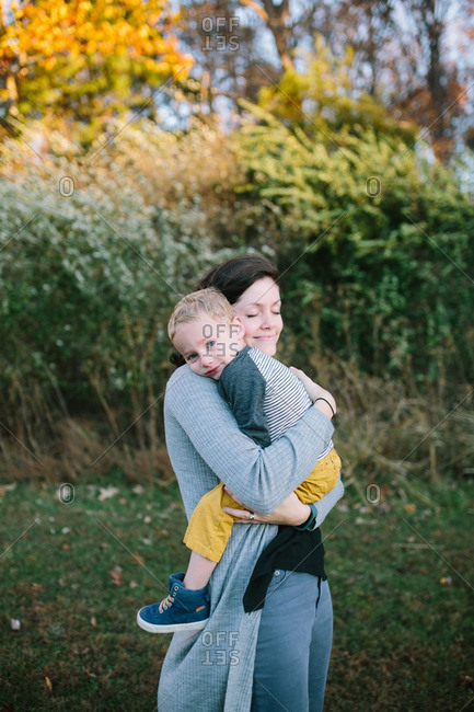 Woman hugging her toddler son outdoors in autumn