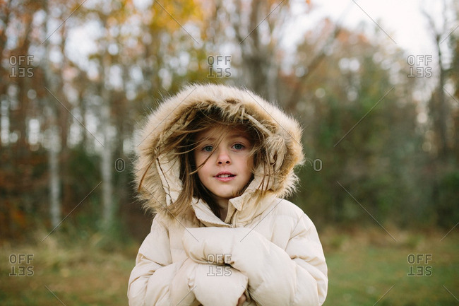 Portrait of young girl in hooded coat in autumn