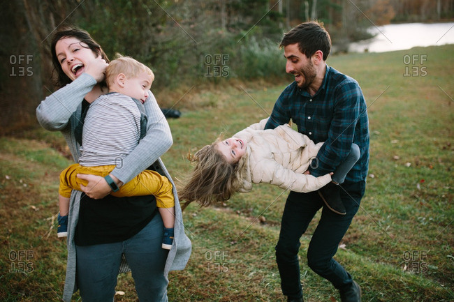 Playful family of four outdoors in autumn