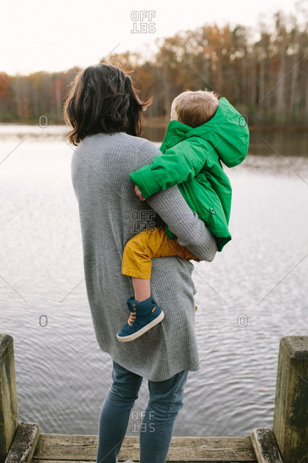 Back view of mother holding toddler son on dock at lake