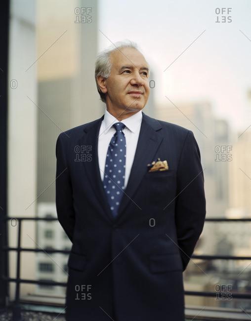 Senior businessman standing on a balcony.