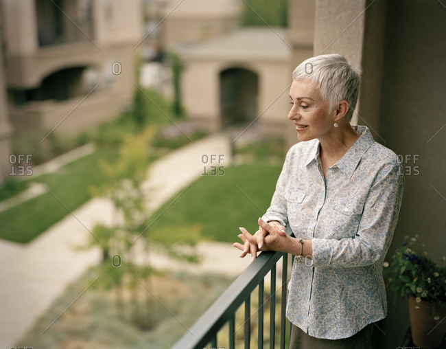 Smiling woman standing on a balcony.