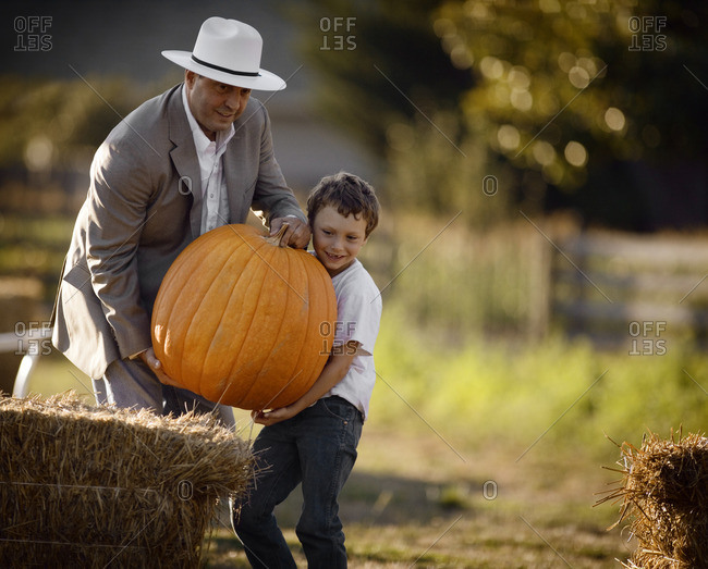 Father and son carrying a large pumpkin.