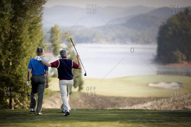 Two men walking across a scenic golf course.