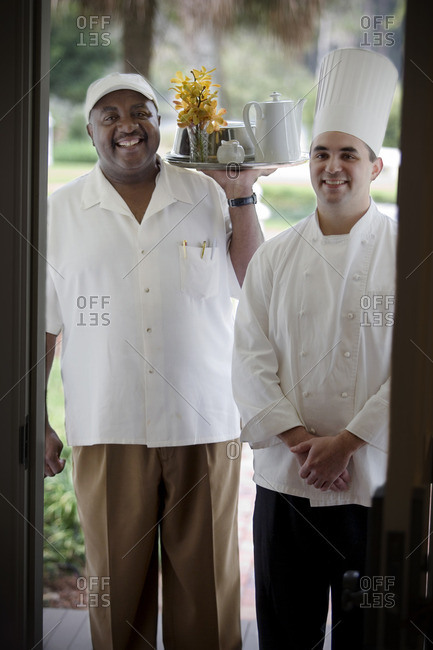 Waiter and a chef arriving with a room service tray.