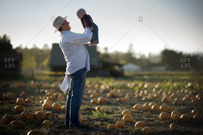 Father holding up his baby son in a pumpkin patch.