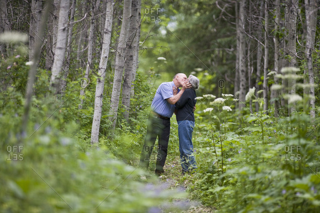 Senior couple sharing a kiss on a forest path.