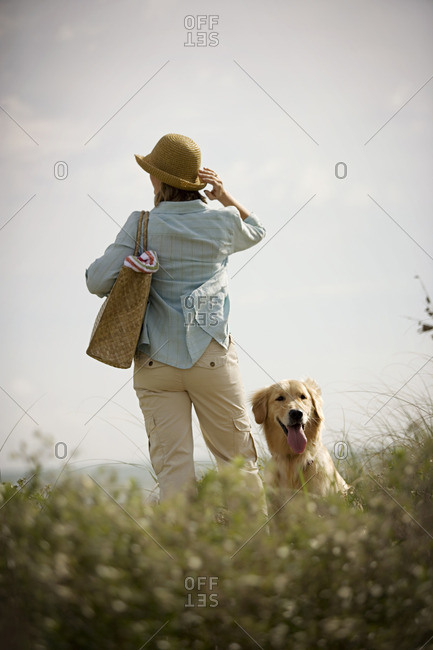 Woman looking out at a beach view with her dog by her side.