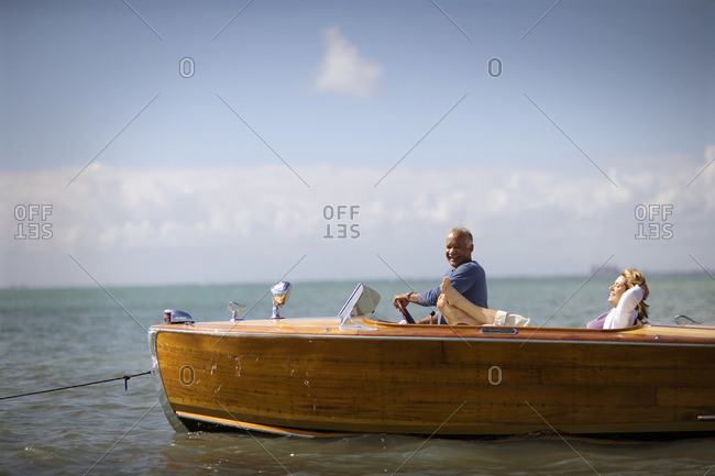Mature couple relaxing together on a vintage wooden boat.