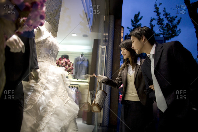 Couple looking in the window of a bridal store.