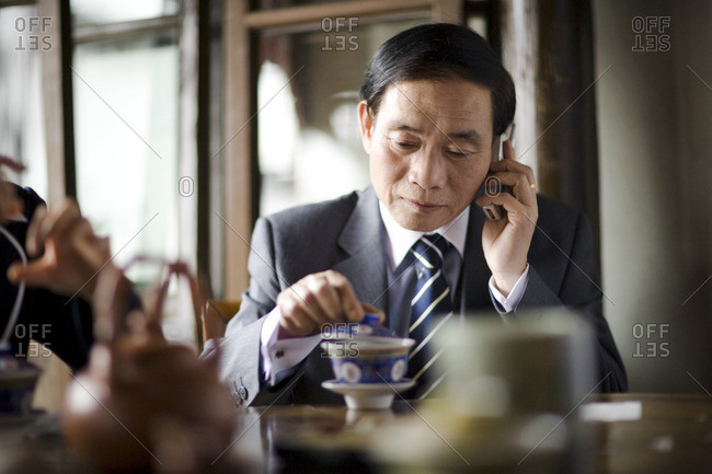 Businessman on the phone in a tea room.