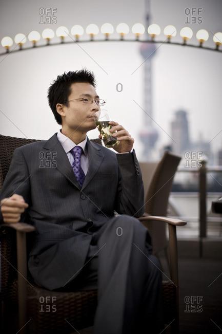Businessman enjoying a drink at a rooftop bar.
