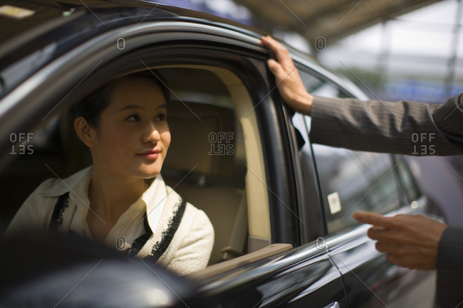 Businesswoman talking to someone out of her car window.