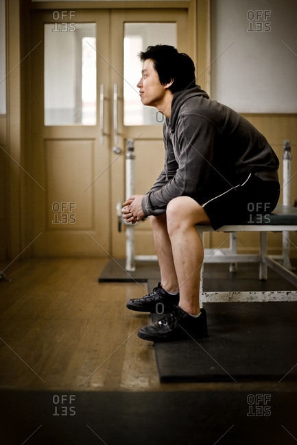 Young man sitting on a bench in a gym.