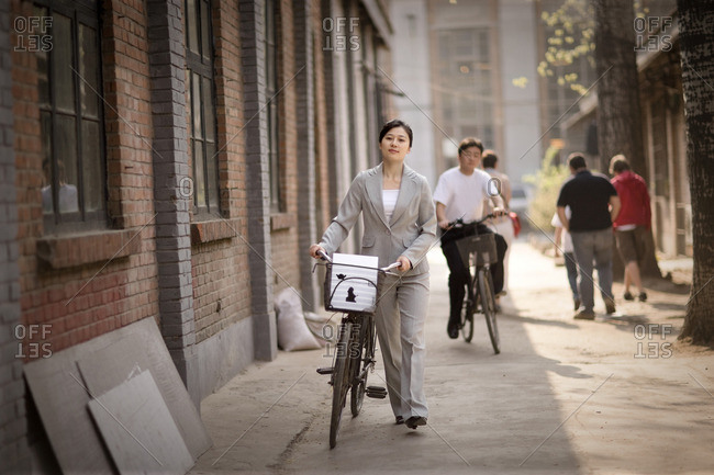 Businesswoman walking her bicycle down an alley.