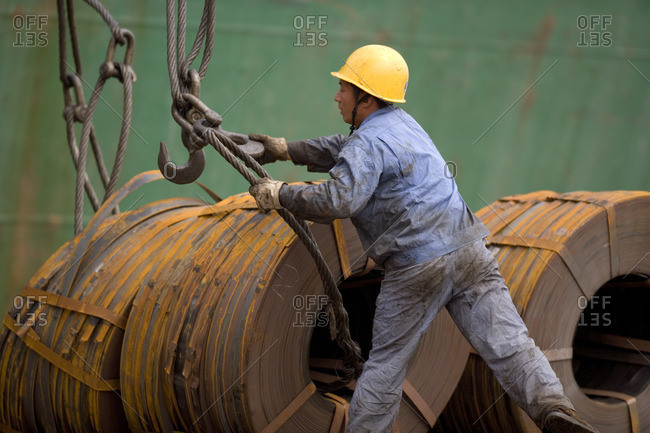 Worker attaching materials to hooks to be loaded onto a ship.