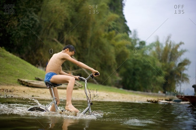 Young boy riding his bike in a river.