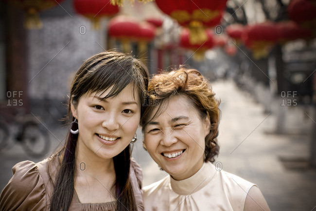 Two smiling women on a street decorated with hanging lanterns.