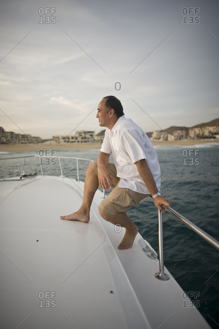 Man sitting on the railings of a boat.