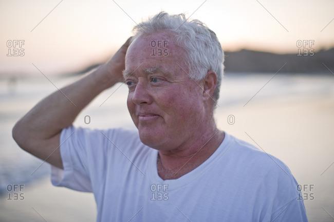 Senior man on the beach at sunset.