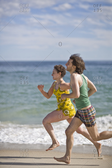 Young couple racing each other on the beach.