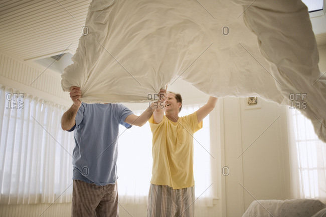 Two men making the bed together.
