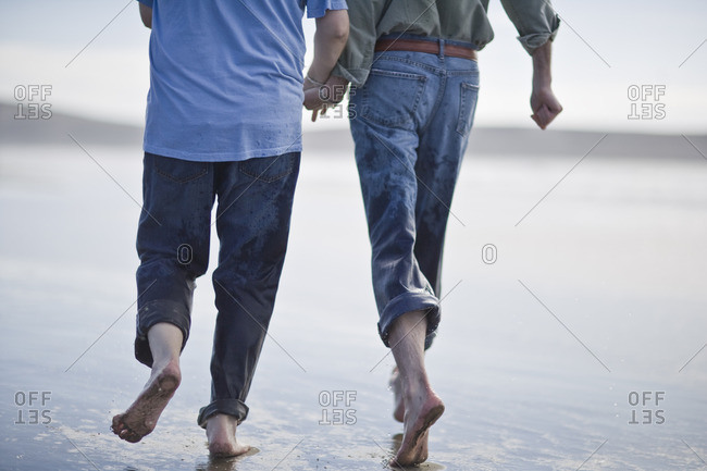 Couple walking barefoot on the sand.