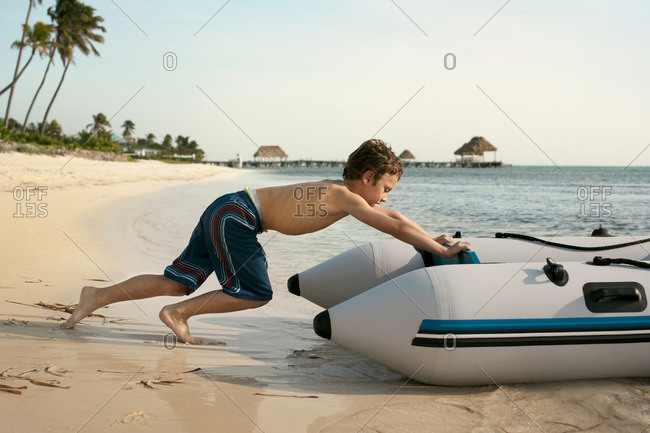 Young boy pushing his boat into the water.