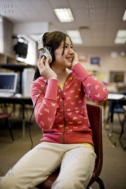 Young girl listening to headphones in a classroom.