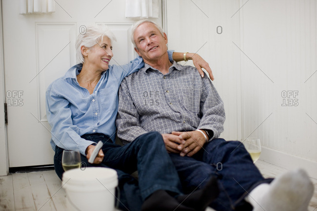 Couple relaxing with a glass of wine after doing some DIY.