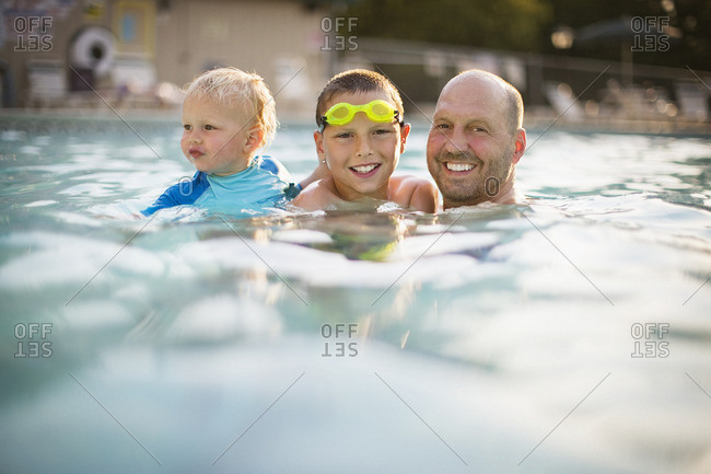 Father and his two sons swimming in a swimming pool