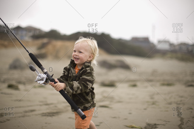Toddler boy holding a fishing rod on the beach.
