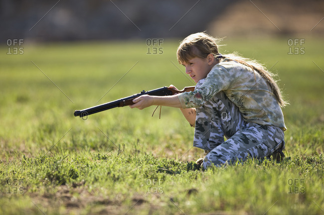 Young girl hunting with a small gun.