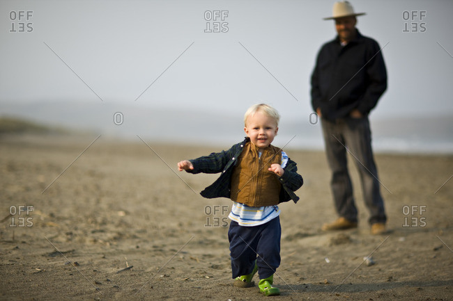 Father and his toddler son on the beach.