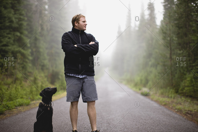 Man standing on a forest road with his dog.
