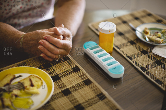 Woman sitting at the dining table with her daily medication.