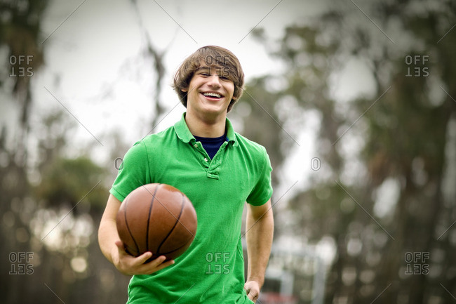 Smiling teenage boy playing basketball.