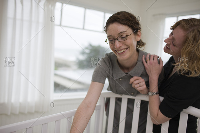 Two women standing over a baby's crib.