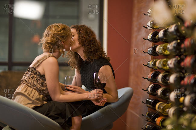Lesbian couple sharing a kiss while on a romantic date.