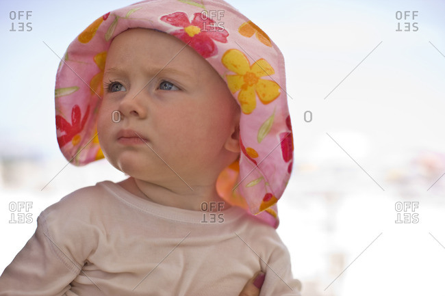 Young girl wearing a floral patterned sun hat.