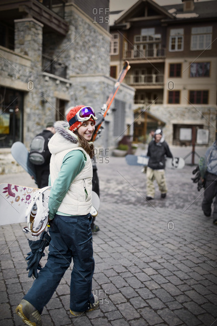 Snowboarder arriving at a ski resort for a day on the slopes.