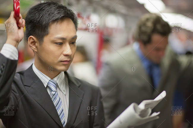 Businessman reading the newspaper on the commute to work.