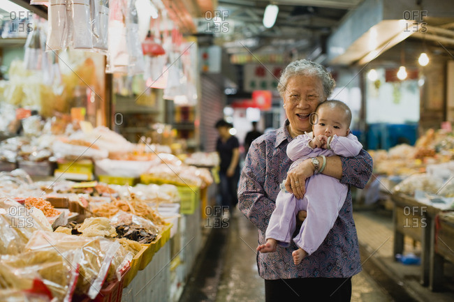 Senior woman holding her baby grandchild in a market.