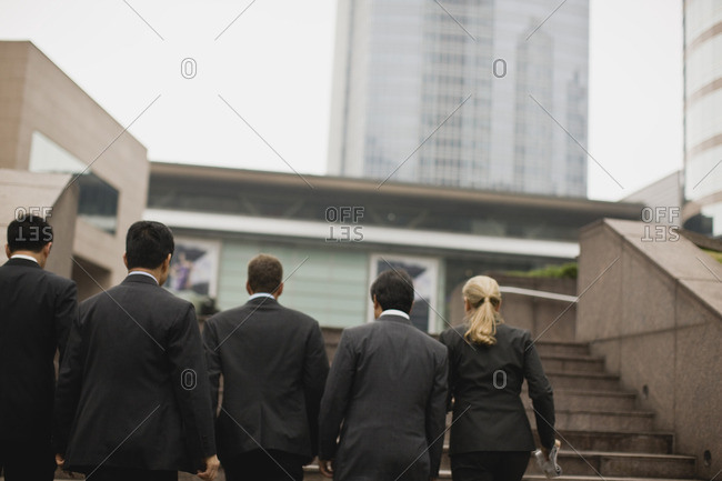 Group of businesspeople walking up the stairs to their office.