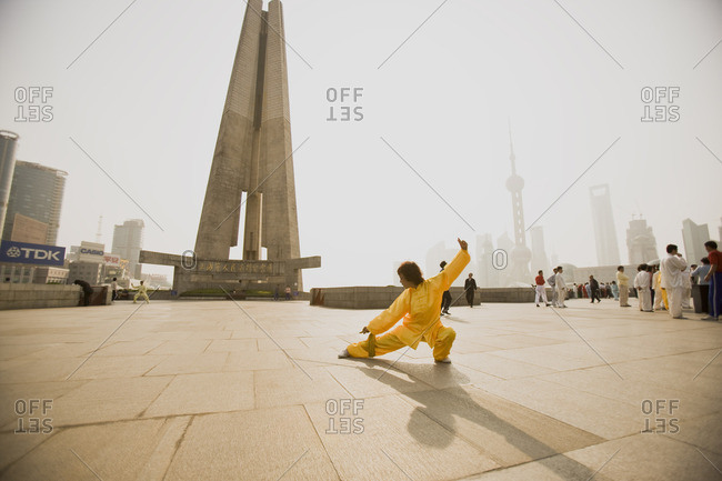 December 7, 2016: Woman practicing tai chi in a city square in Shanghai, China.