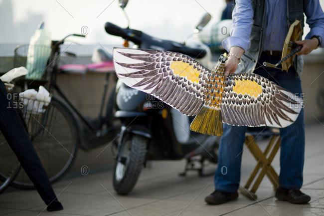 Street vendor showing off a kite shaped like a bird.