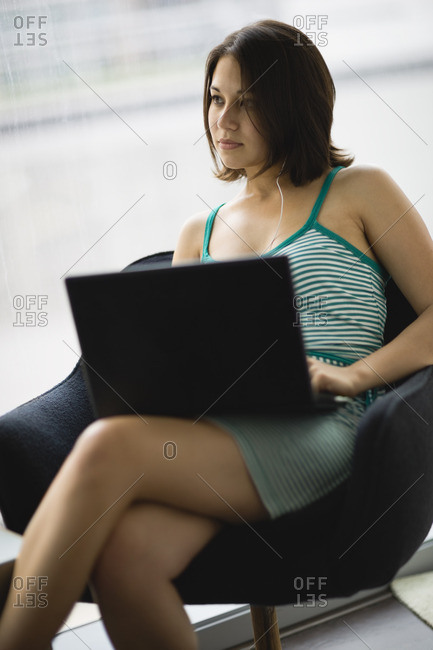 Young woman sitting working on a laptop computer.