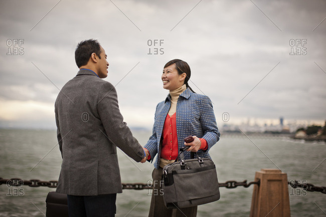 Business colleagues shaking hands by the harbor.
