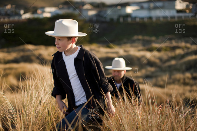 Father and son walking in long grass.